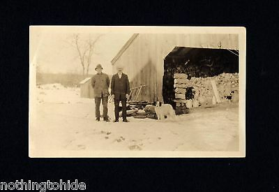 Photo of Spaniel Mix Dog With Men in Front of Barn Circa 192?