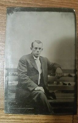 Tintype photograph of young man on park bench