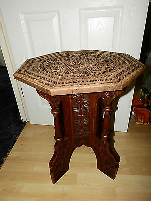 A carved Moorish hardwood octagonal top table, decorated with geometric designs