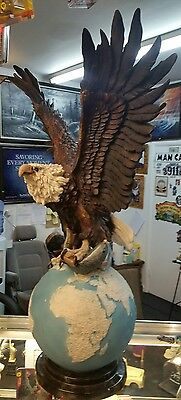 eagle standing on world statue with fish solid eagle statue large