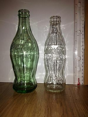 One 1915 Coca-Cola contour bottle replica and one modern replica.