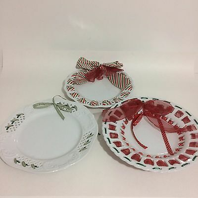 Three White Porcelain Plates With Cut Outs And Red White Green Decorative Ribbon