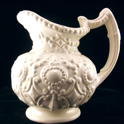 Camark Pottery Ivory Pitcher with Ornate Embossed Design