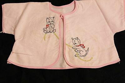 Pink baby blanket,bib & shirt embroidered with cats playing on the items.