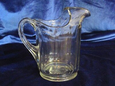Antique glass pitcher, panel design with ice lip and embossed sunburst on bottom