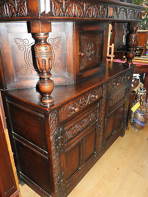 A 1920's Oak Buffet Sideboard, in the Jacobean manner with carved cupboard doors