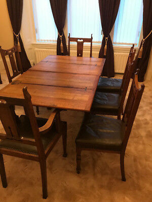 Arts and Crafts extending oak dining table with 6 oak dining chairs