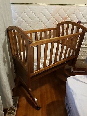 lightbrown wooden baby craddle on wheels