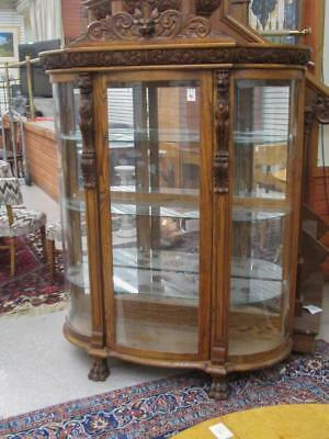 A CARVED OAK AND CURVED GLASS CHINA DISPLAY CABINE Lot 96