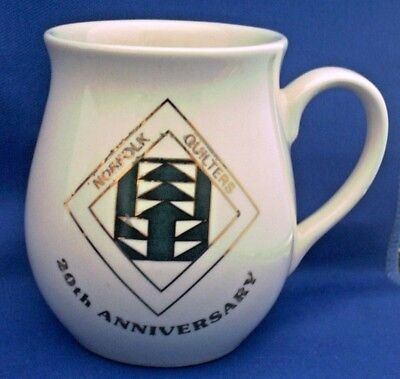 HOLKHAM POTTERY. SMALL MUG ADVERTISING THE NORFOLK QUILTERS (20th ANNIVERSARY)
