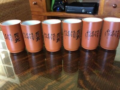 a set of 6 Japanese calligraphy pottery sake cups. stamped and signed.
