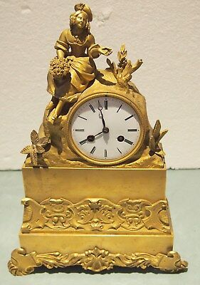 A French Empire Ormolu Mantle Clock With A Figure Of Beauty & Bouquet Flowers