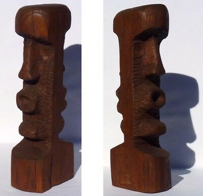 Wood carving that has two faces on opposite sides. Resembles Easter Island Heads