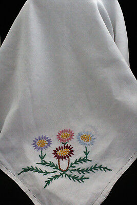 Vintage white linen tablecloth with hand embroidered coloured flowers.