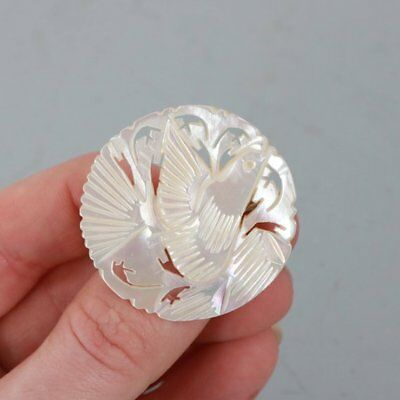 A vintage 1930s iridescent mother of pearl round bird brooch