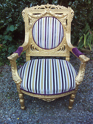 An impressive French Louis style heavily gilded armchair with a striped fabric.