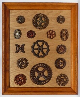 A collection of 15 old, decorative cast iron faucet handles mounted & framed.