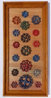 A collection of 18 old, decorative cast iron faucet handles mounted & framed.