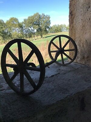 Pair of ancient rustic french heavy metal cartwheels, with centre axel piece