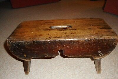 Antique hand made country- style wooden low stool with hand hold in the centre