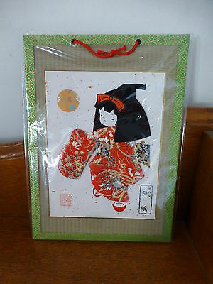 Japanese origami paper art on woven bamboo board frame girl in red kimono New