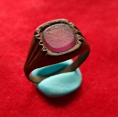 Ancient east Roman bronze ring decorated with purple glass garnet stone  .