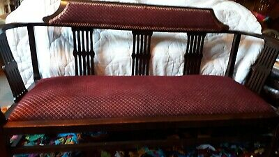 Edwardian original love seat, burgundy upholstery, curved arms, carved supports.