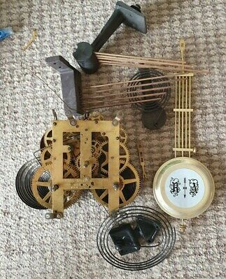 assorted clock parts including chime bars and movement
