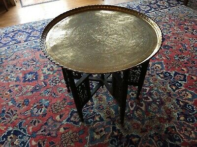 large antique Oriental  brass  table on carved wooden legs  25 cms diameter