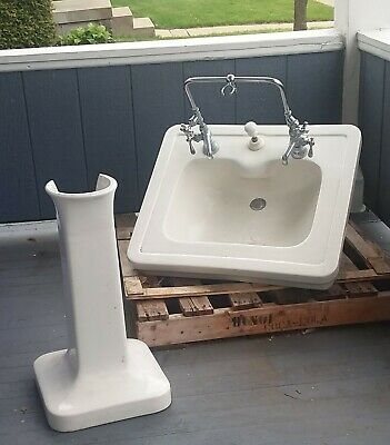 White antique pedestal sink with facuets and hardware