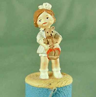 Sewing Thimble Girl Character Holding Teddy Bear on Blue Thread Spool wth Needle