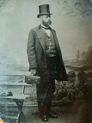 tintype portrait of post Civil War man wearing top hat and carrying a small bag