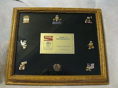 (8) 1984 Olympic Coca Cola commemorative pins in glassed frame