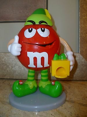 M&M Red dressed as an elf candy dispenser