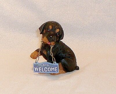 Rottweiler puppy with 'Welcome' sign