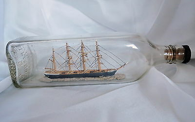 Vintage or antique four mast sailing ship in an early Walker's whisky bottle