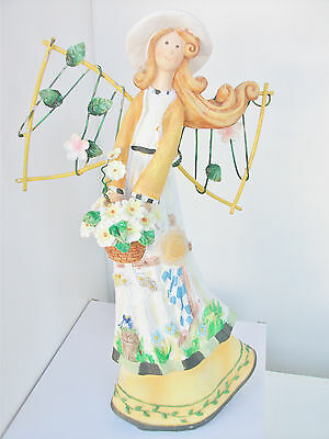 Tall fairy figurine holding flower basket metal wing carved flowers on dress