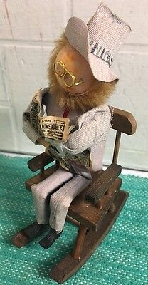 Small Wooden Man In Rocking Chair Reading Paper