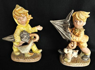 2 Adorable figurines of a Girl w/umbrella and goose and a Boy w/umbrella and dog