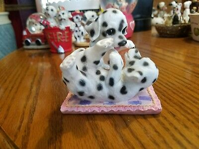 Dalmatian puppies playing on blanket figurine