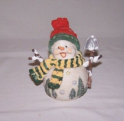 A Smiling Round Decorative Snowman Figurine With Shovel