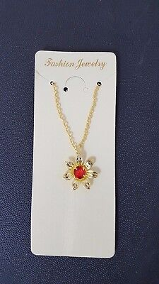 A gold necklace with a pendant in the shape of a flower and a red diamond