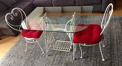 glass top table with singer sewing machine base and two chairs