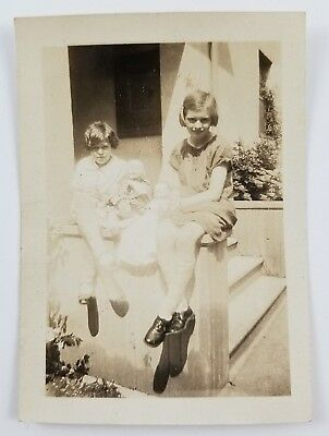 Snapshot Photograph Two Girls with Dolls Sitting on Ledge Circa 1920s