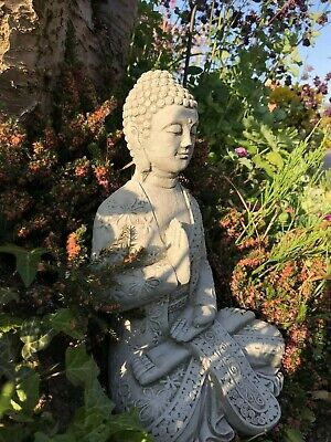 Buddha hand across chest resting stone garden ornament zen meditating