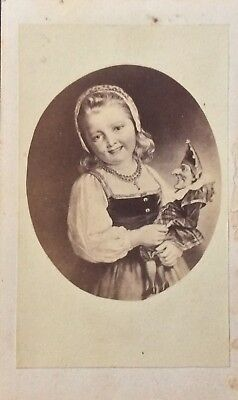 CDV Genre filler card of a young girl with a marionette (smiling)