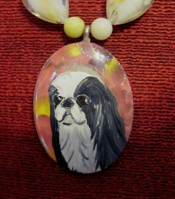 Japanese Chin hand painted on oval, metal backed pendant/bead/necklace