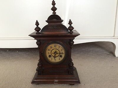Antique dark wood clock with key and in working order