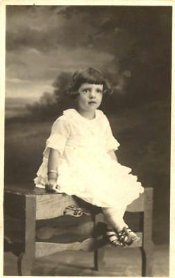 Rppc Vintage photo of Darling little girl sitting on bench