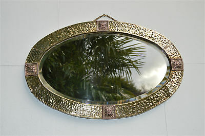 Arts and Crafts oval beaten brass framed wall mirror stylised flower design